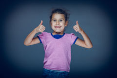 Jugendlich Mädchen stellt dar, dass Geste so auf einem Grau übergibt Stockbilder