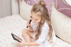 Jugendlich Mädchen, welches das Make-up sitzt auf einem Bett anwendet stockbild