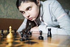 Jugendlich Mädchen, welches die Niederlage spielt Schach macht lizenzfreie stockbilder