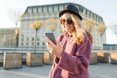 Jugendlich Mädchenhippie im Hut und in den Gläsern mit Handy, goldene Stunde lizenzfreies stockfoto