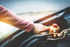 Jugendlich Mädchenkontrolle der Maschinenheizkörper des Autos stockfotografie