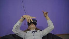 Jugendlich M?dchen in den virtuellen Gl?sern auf einem purpurroten Hintergrund stock footage