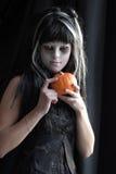 Jugendlich Mädchen, das als Hexe für Halloween über dunklem Hintergrund trägt Stockfoto
