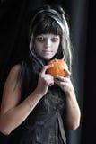 Jugendlich Mädchen, das als Hexe für Halloween über dunklem Hintergrund trägt Stockfotografie