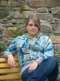 Jugendlich Mädchen, das auf der Bank sitzt Lizenzfreie Stockfotos