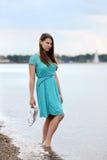 Jugendlich Mädchen, das Sandalen auf dem Strand hält Stockbild