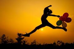 Jugendlich Mädchen mit den Ballonen, die auf die Natur springen Stockbild