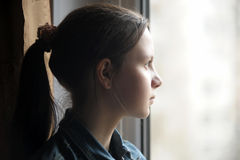 Jugendlich Mädchen, welches heraus das Fenster schaut Lizenzfreies Stockfoto