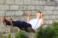 Jugendlich mit dem blonden Haar, das eine Kette swing2 reitet lizenzfreies stockbild