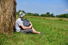jugendlich mit dem Rucksack, der nahe bei Stapel Stroh sitzt stockbilder