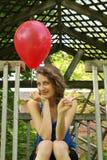 Jugendlich mit einem Ballon, der Siegzeichen tut Lizenzfreies Stockfoto
