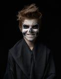 Jugendlich mit Make-up des Schädels im schwarzen Mantel lacht stockfotografie