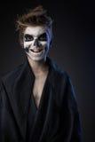 Jugendlich mit Make-up des Schädels im schwarzen Mantel lacht lizenzfreies stockfoto