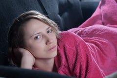 Jugendlich mit Pyjamas auf der Couch Lizenzfreies Stockbild