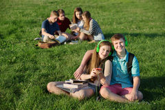 Jugendlich Paare, die draußen sitzen lizenzfreies stockbild