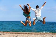 Jugendlich Paare, die Rückseiten gebend springen Lizenzfreie Stockfotografie