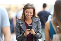 Jugendlich Plaudern am intelligenten Telefon, das durch Leute umgibt stockfoto