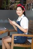 Jugendlich schönes Mädchen des thailändischen Studenten, das ihr intelligentes Telefon und Lächeln verwendet stockfotos