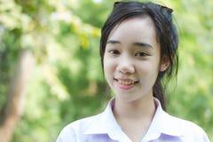 Jugendlich schönes Mädchen des thailändischen Studenten entspannen sich und lächeln im Park Lizenzfreies Stockfoto
