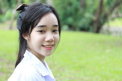 Jugendlich schönes Mädchen des thailändischen Studenten entspannen sich und lächeln im Park Lizenzfreies Stockbild