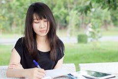 Jugendlich schönes Mädchen des thailändischen Studenten schreiben ein Buch, das in Park sitzt Lizenzfreies Stockfoto