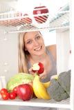 Jugendlich schauende Nahrung im Kühlraum Stockbild