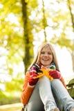 Jugendlich sitzender Fall des glücklichen blonden Mädchens Wald Stockbilder