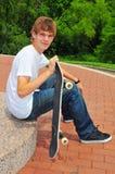 Jugendlich Skateboardfahrer im Ruhezustand am Park Lizenzfreie Stockfotos