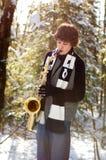 Jugendlich spielendes Saxophon im Schnee lizenzfreie stockfotografie