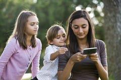 Jugendlich texting Mädchen, jüngere Geschwisteruhr stockfoto