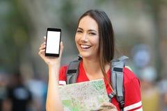 Jugendlich Tourist, der einen Handyschirm zeigt stockbild