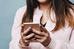 Jugendlich weibliches Simsen an einem intelligenten Telefon mit festem blauem Hintergrund und rosa Pelz-Jacke lizenzfreie stockfotografie