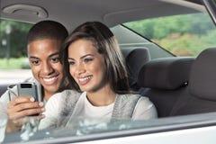 Jugendliche auf der Rückseite des Autos mit Mobiltelefon Stockfotografie