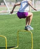 Jugendliche in den purpurroten kurzen Hosen, die über gelbe Hürden springen lizenzfreie stockfotografie
