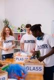 Jugendliche in den weißen T-Shirts, die zusammen Glas und Plastik sortieren stockfoto