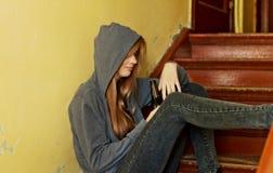 Jugendliche deprimierte Frau, die auf dem Treppenhaus sitzt und ein Bier trinkt Lizenzfreie Stockbilder