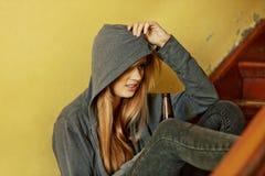 Jugendliche deprimierte Frau, die auf dem Treppenhaus sitzt und ein Bier trinkt Lizenzfreie Stockfotos