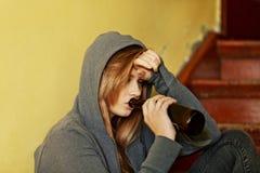 Jugendliche deprimierte Frau, die auf dem Treppenhaus sitzt und ein Bier trinkt Lizenzfreie Stockfotografie
