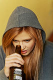 Jugendliche deprimierte Frau, die auf dem Treppenhaus sitzt und ein Bier trinkt Stockfotos