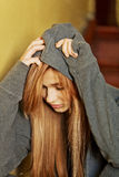 Jugendliche deprimierte Frau, die auf stairscase sitzt Stockbild