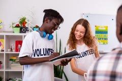 Jugendliche, die Anmerkungen machen, nachdem wenig in der freiwilligen Organisation sortiert worden ist stockfotografie