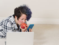 Jugendliche, die Apfel bei der Anwendung ihres Handys und listeni isst Lizenzfreie Stockfotos
