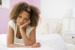 Jugendliche, die auf Bett liegt Lizenzfreies Stockbild