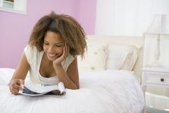Jugendliche, die auf Bett-Messwert liegt Lizenzfreie Stockfotos