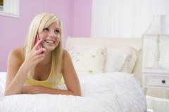 Jugendliche, die auf Bett unter Verwendung des Handys liegt Stockfotografie