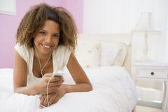 Jugendliche, die auf Bett unter Verwendung des MP3-Players liegt Stockbild
