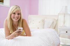 Jugendliche, die auf Bett unter Verwendung des MP3-Players liegt Lizenzfreies Stockbild