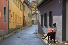 Jugendliche, die auf der Bank auf alter Stadtstraße sitzt Stockfotografie