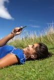 Jugendliche, die auf Gras mit MP3-Player liegt Stockfotografie