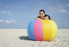 Jugendliche, die auf großem buntem Wasserball sich entspannt Stockfoto